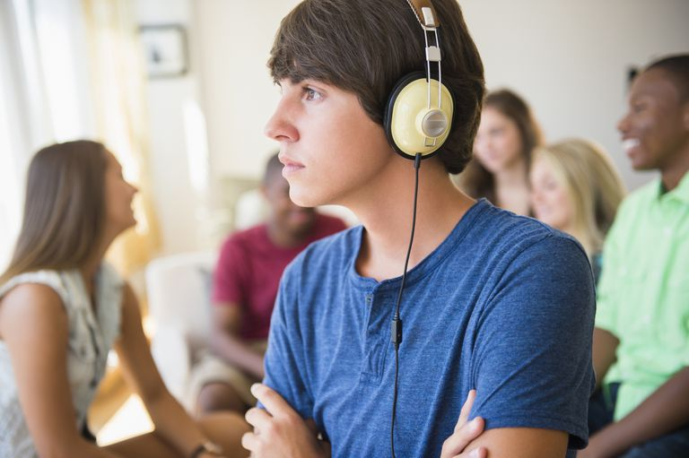 Teenage boy listening to headphones at a party