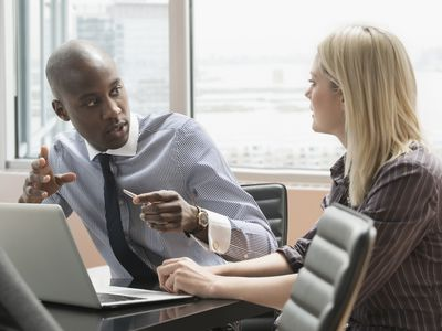 Photo of a man and woman talking in front of a computer
