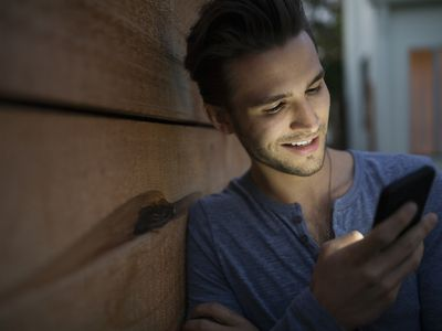 man smiling while looking at cell phone