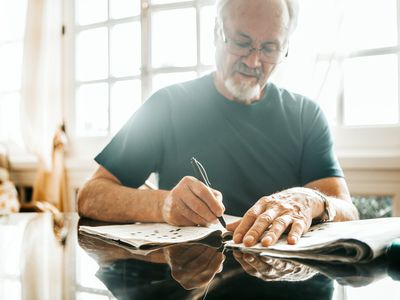 Older man works on a crossword puzzle