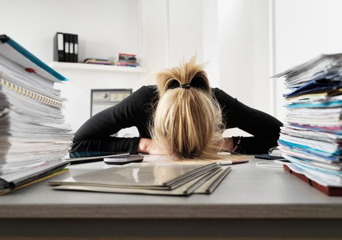 Woman surrounded by stacks of papers with her head on her desk