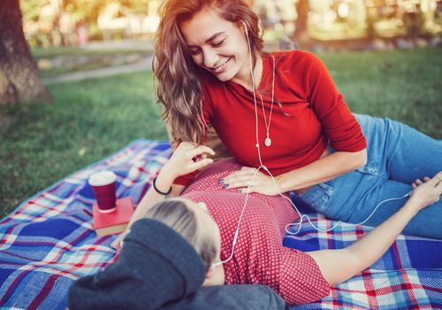 A young lesbian couple lays on a blanket together in a park.