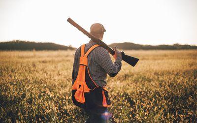 Man walking through a field with a shot gun over his shoulder