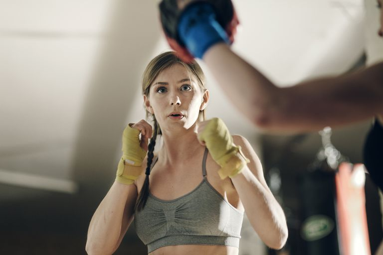 A woman holding her gloved hands up during boxing training