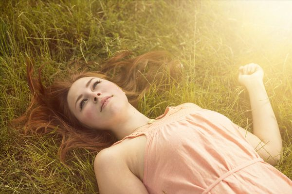 Ethereal looking woman laying in a field