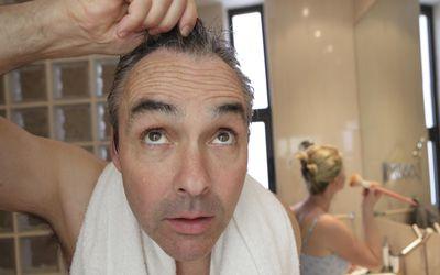 Man checking hair line in mirror