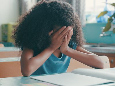 Black girl sitting in a classroom holding her hands over her face