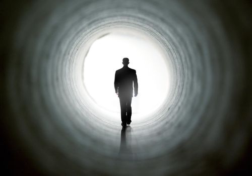 Man walking through a tunnel toward the light