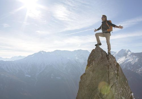 Hiker stands on pinnacle summit, arms outstretched