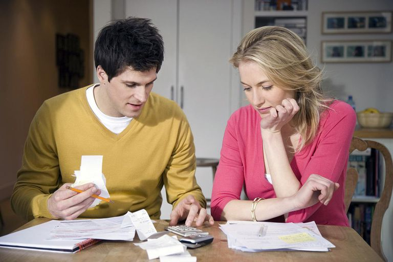 Young couple with receipts and documents using calculator