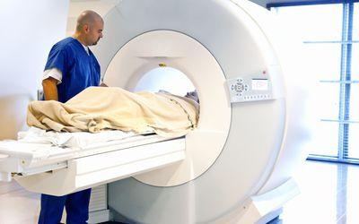 Medical professional putting patient in MRI scan machine.