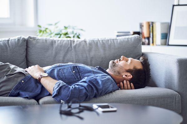 Man lying on couch with eyes closed.