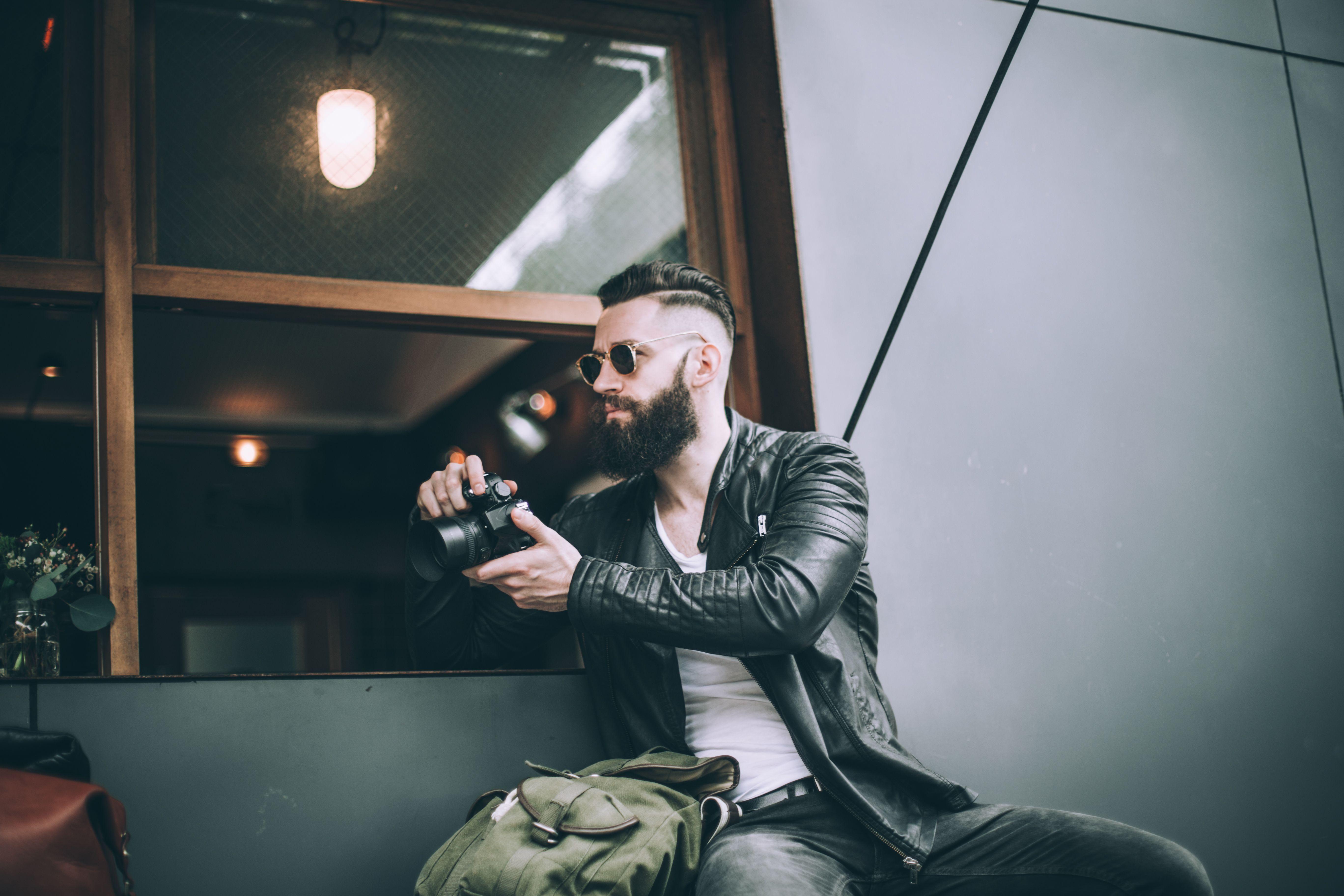 Man wearing sunglasses and leather jacket, holding camera