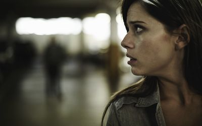 paranoid woman looking over shoulder
