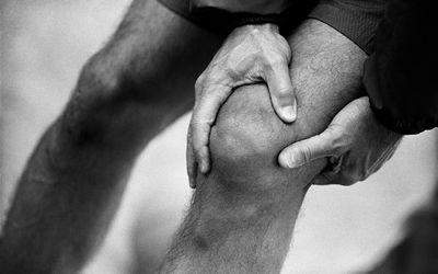 Man Holding Knee