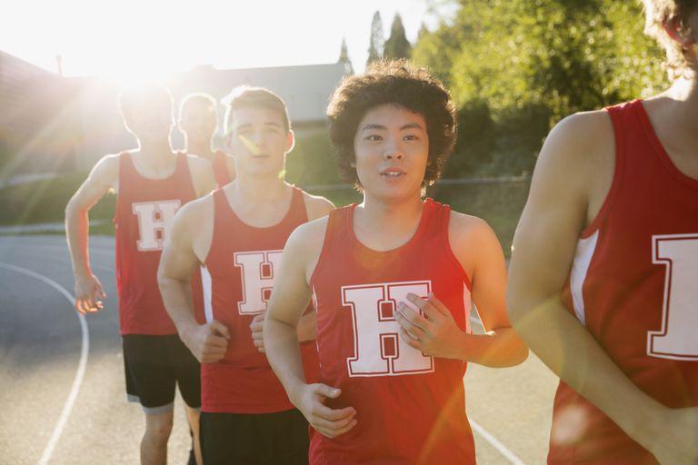 High school boys on sports team running outdoors