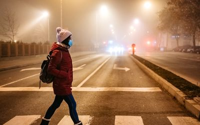 woman wearing a mask walking in a polluted city