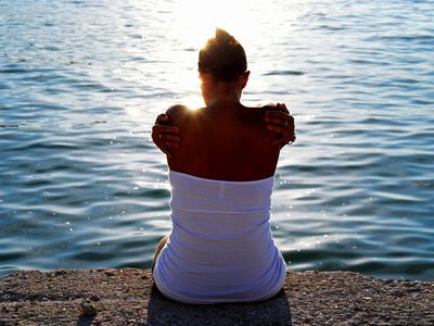 Rear view of young woman sitting by sea