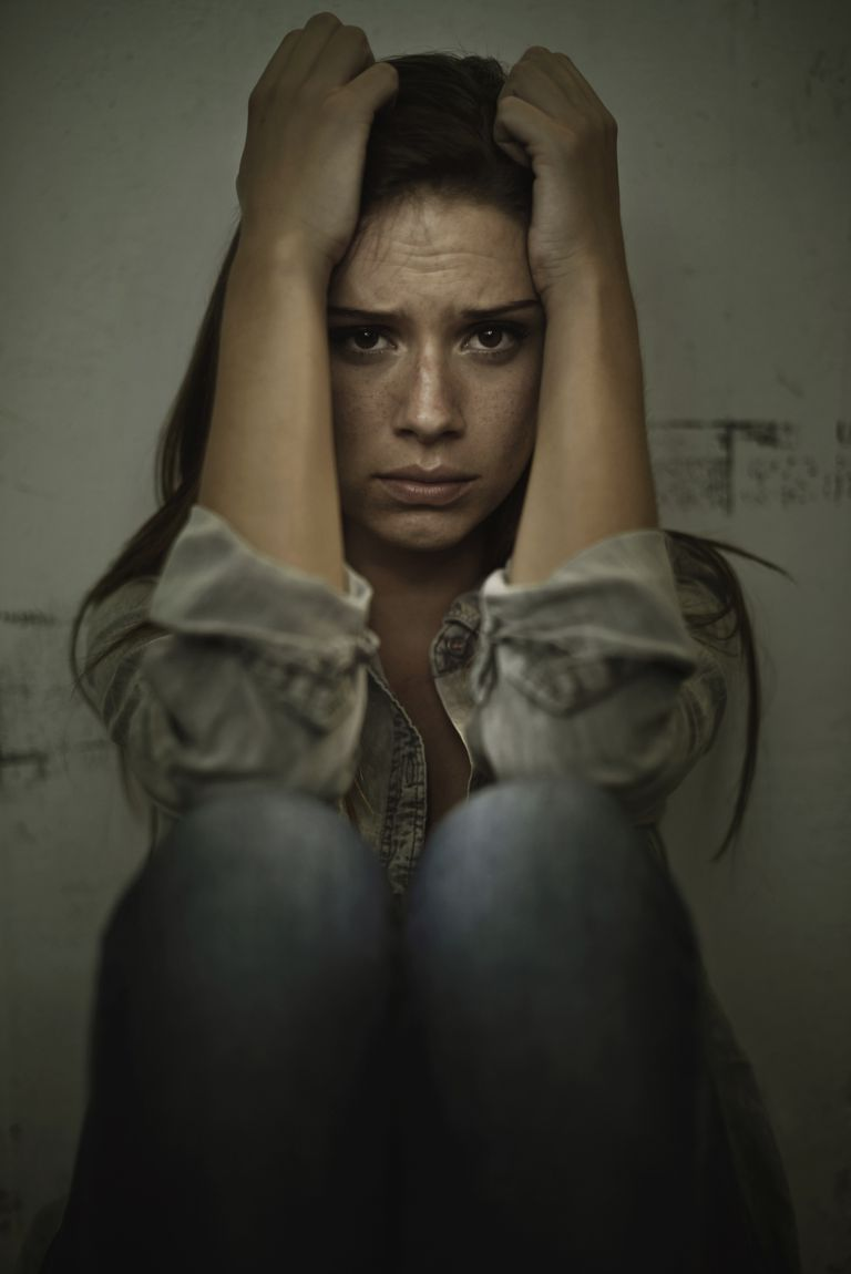 Delirious woman holding head in hands