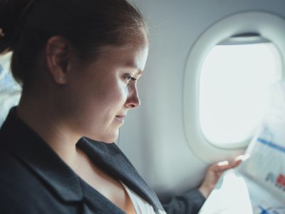 Business woman reading news in plane.