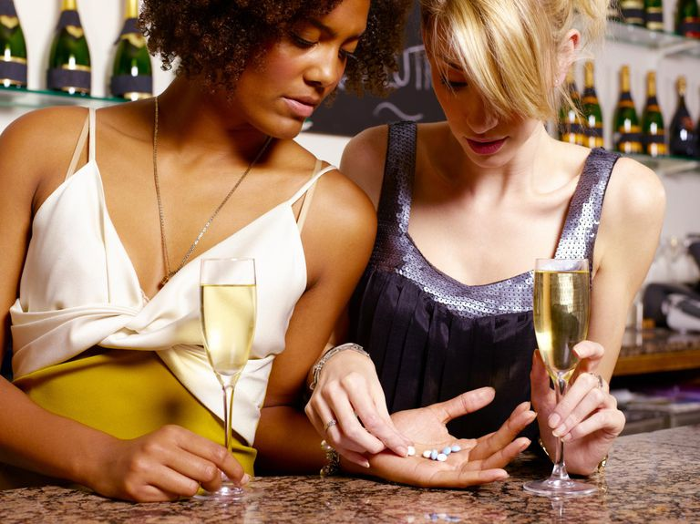 two women sharing pills with wine at a bar