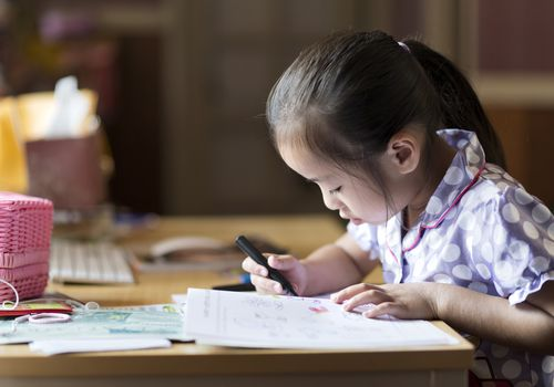 young girl reading and writing