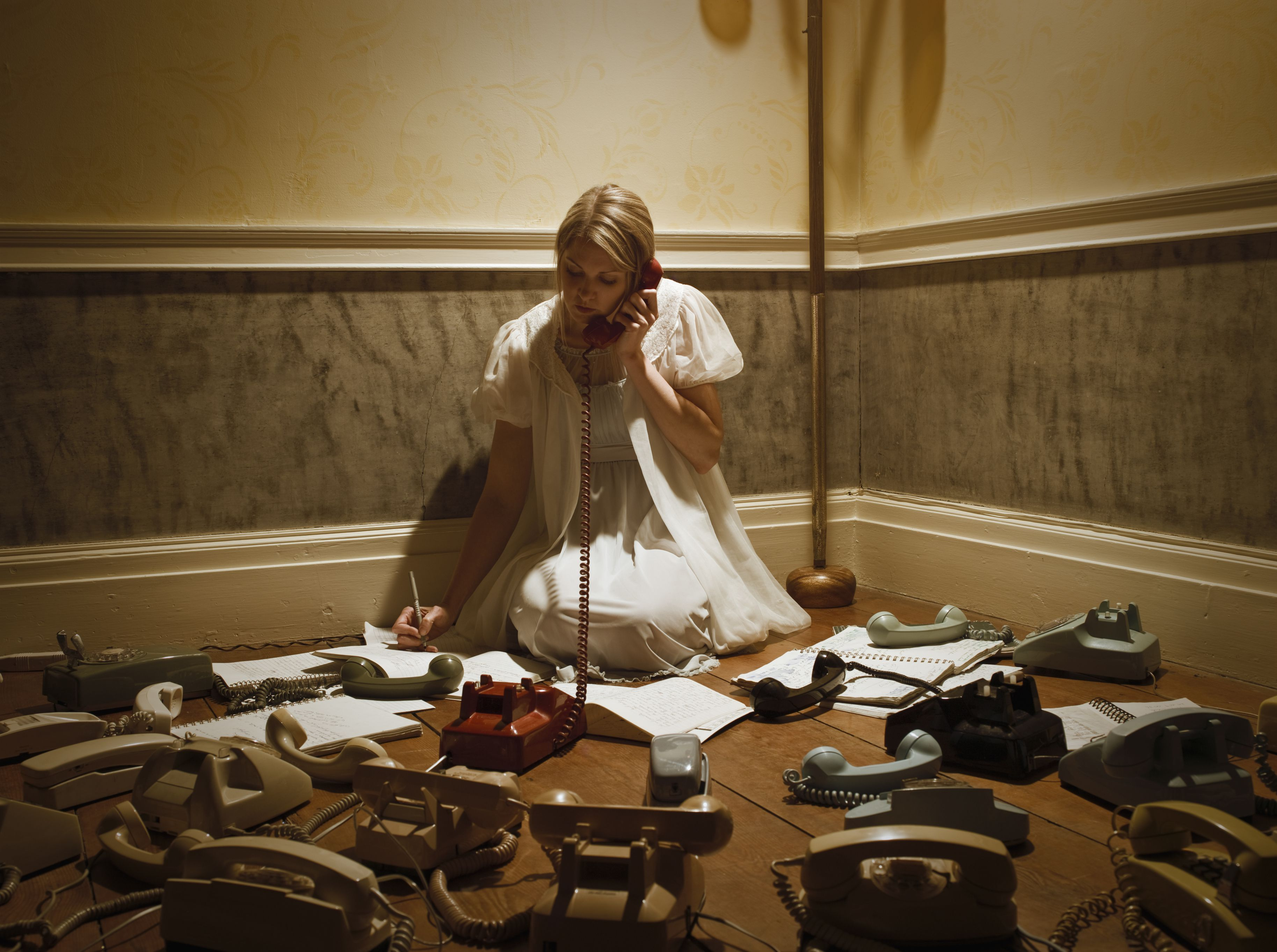 Woman surrounded by telephones