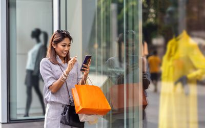 Asian woman using the smart mobile phone for check online shopping order is completed with clothes beside the glassess in store shop with happy action at department center