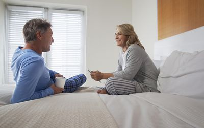 Middle aged couple sitting on bed talking and smiling