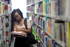 Black student looking at books in the library