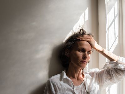 Tense woman leaning against a wall
