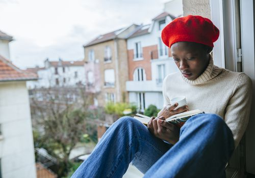 Woman reading a book on a window ledge