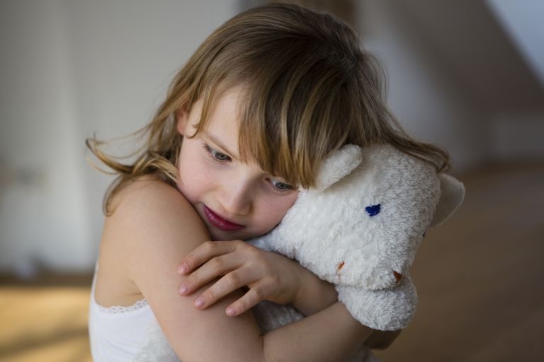 Sad girl hugging a stuffed animal