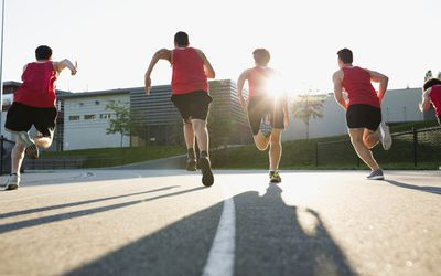Teens running track at school.