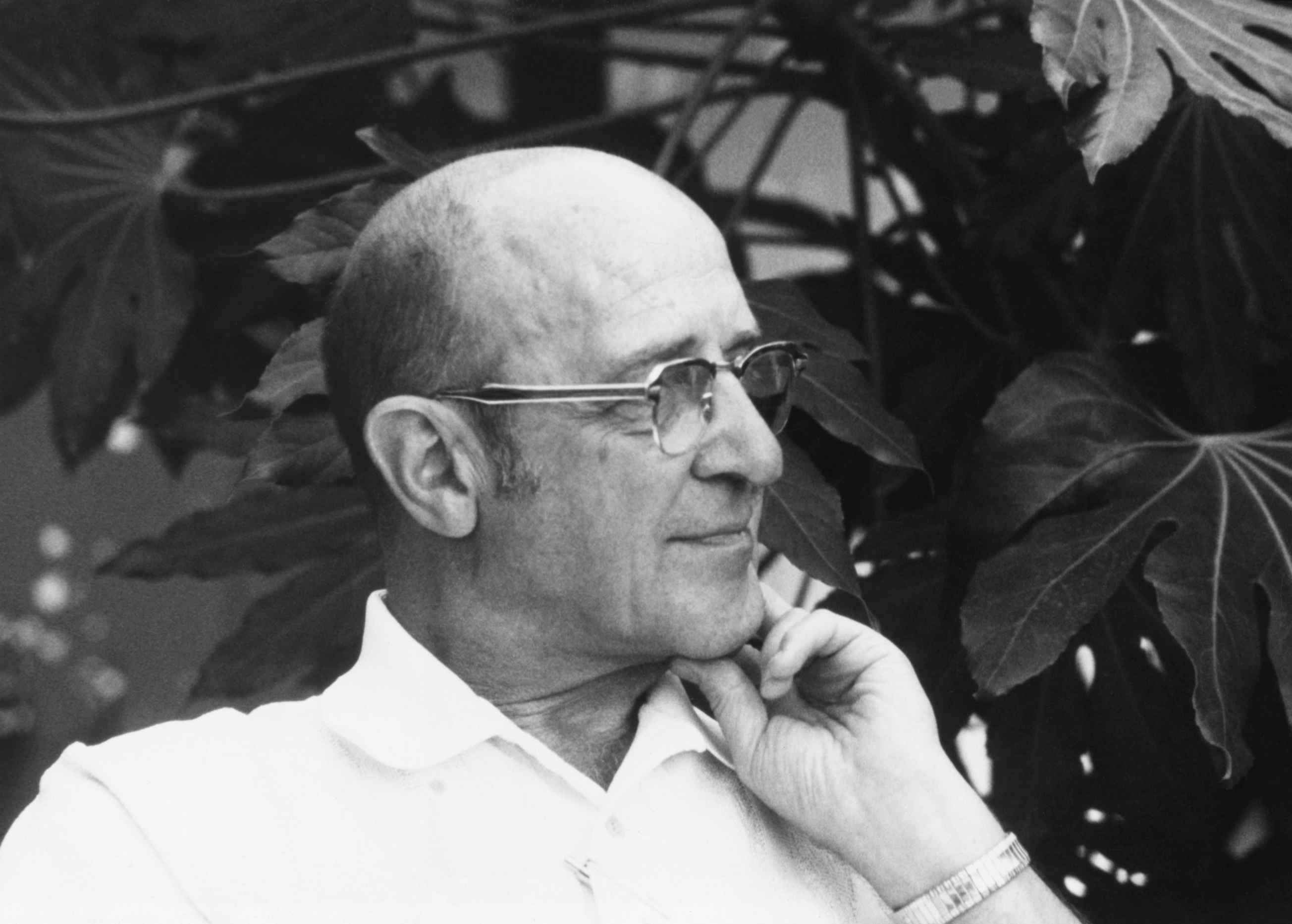 Carl Ransom Rogers sitting in front of a plant, looking away