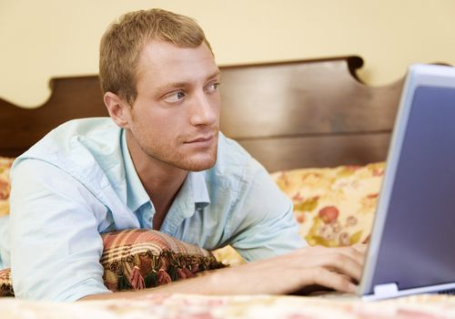 Man on his laptop in the bedroom