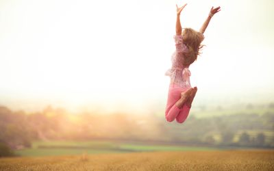 Girl jumping with joy in field