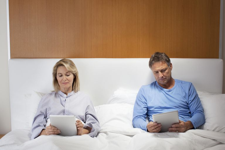 Middle aged couple using tablet in bed