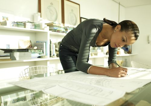 Woman working on a plan, bending over to write on a glass desk