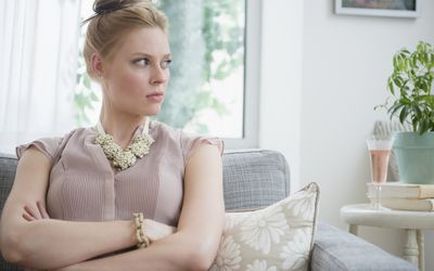 angry woman with crossed arms sitting on couch