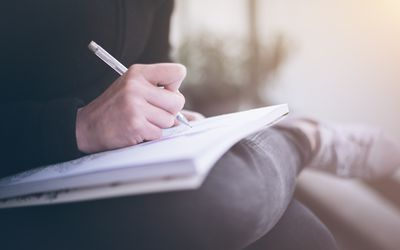 Close-Up Of Person Writing In Book