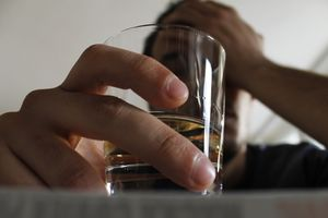 Man holding glass of alcohol, resting his head in his hand