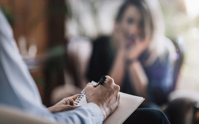 A therapist taking notes as a client talks about her problems.