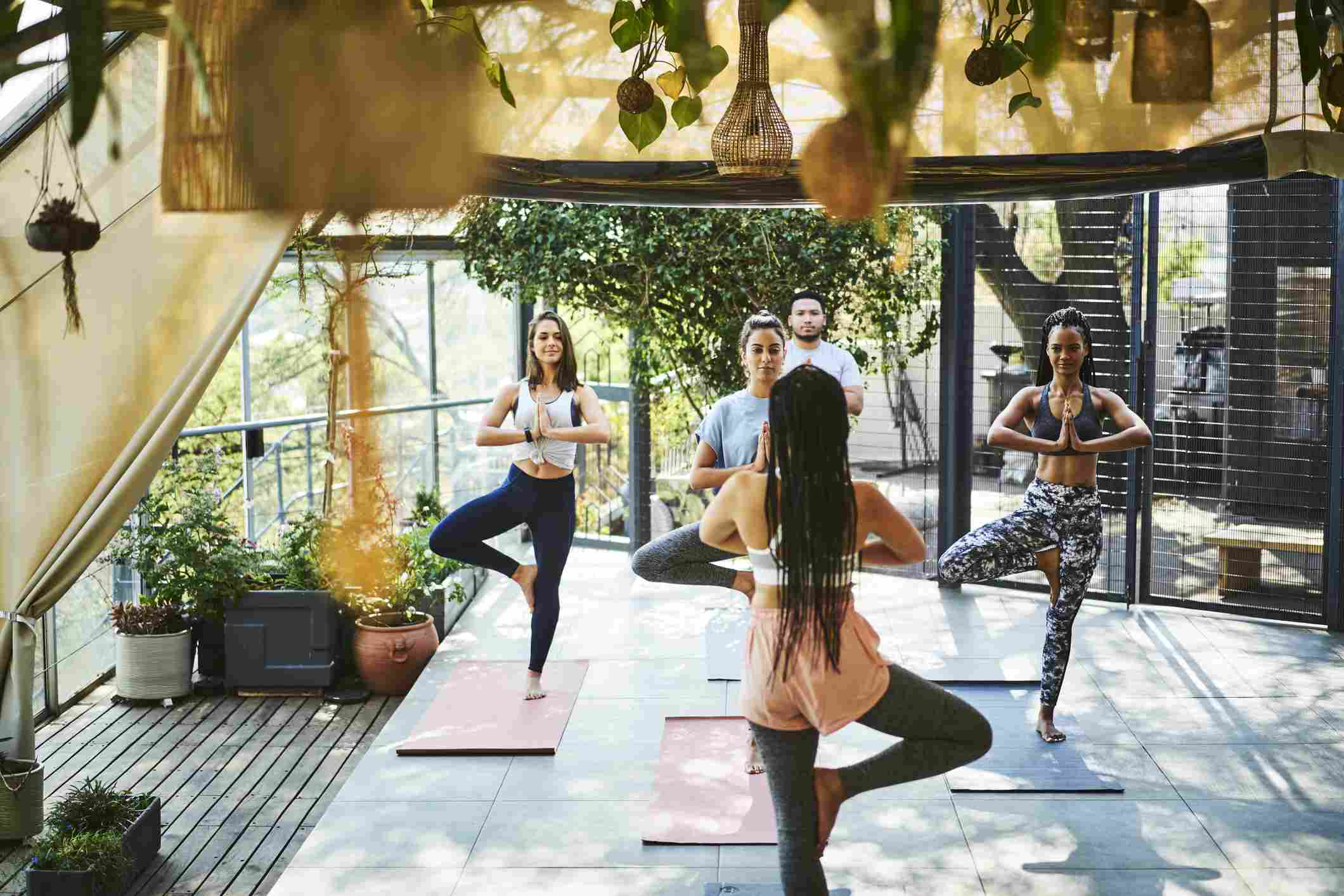 Instructor teaching tree pose to clients on porch
