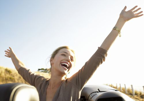 Young woman raises arms playfully and smiles in the back of a convertible