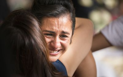 Woman crying with other woman hugging her.