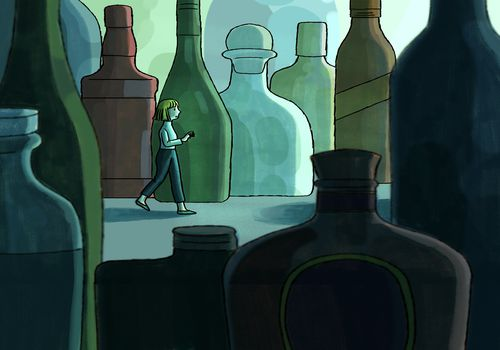 A woman walks among alcohol bottles.
