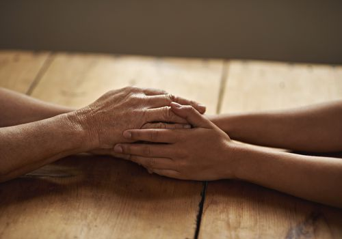 Old and young hands clasped over a table