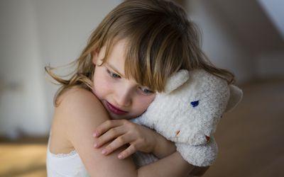 Sad girl hugging a stuffed animal