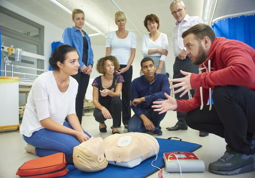 Man teaching a group of people how to do CPR